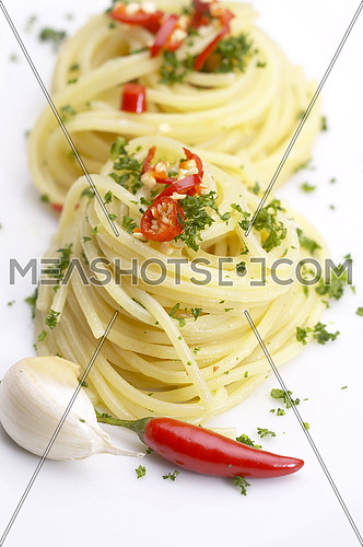 pasta garlic olive oil and red chili pepper closeup on a white dish