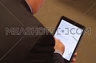 A business man writing on a tablet