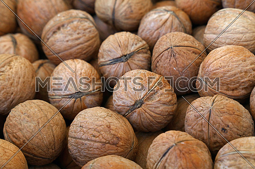 Whole walnuts with brown nutshells on retail market, close up, background, low angle view