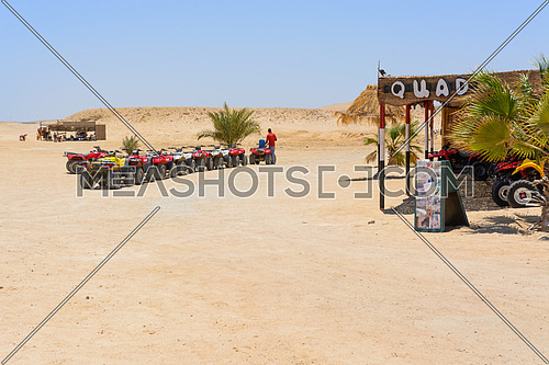 In the picture a row of oblique quad where a man fill up with petrol at the quad and in the background the Egyptian desert
