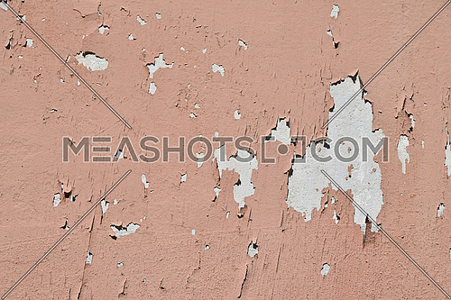 Vintage flakes of old faded pink paint over abandoned grey concrete wall