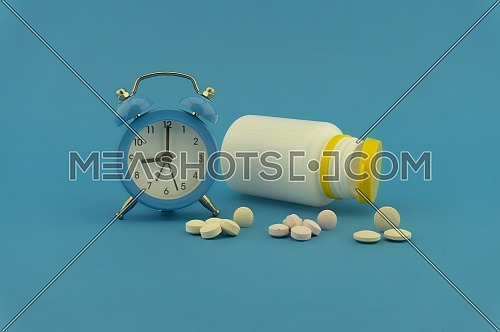 Medication and healthcare concept with pharmaceutical bottle, tablets, and blue alarm clock over a colorful blue background
