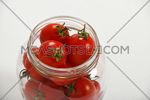 Glass jar full of red cherry tomatoes ready for conservation over white background, high angle view, close up