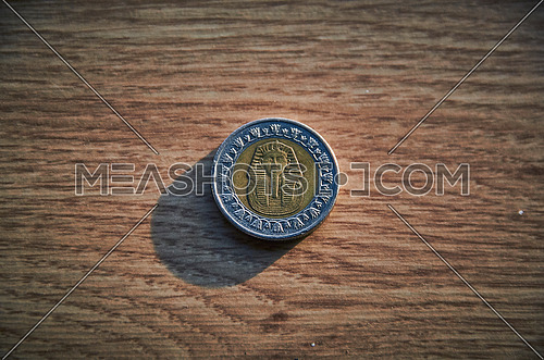 close up for One Egyptian pound coin on pharaoh side with wooden background