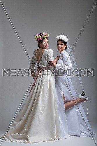 Portrait of two beautiful young bride in wedding dresses isolated on a white background
