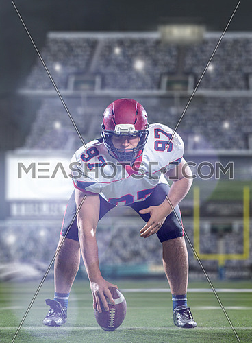 American football player preparing to start the football game on american football field at modern stadium with lights and flares at night