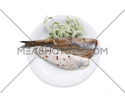 Close up portion of salted pickled herring fish filets with onions and sauce on white plate  isolated on white background, elevated top view, directly above
