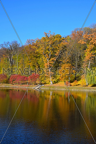Autumn park landscape of colorful yellow and red trees and blue sky with reflection in calm water of pond or lake