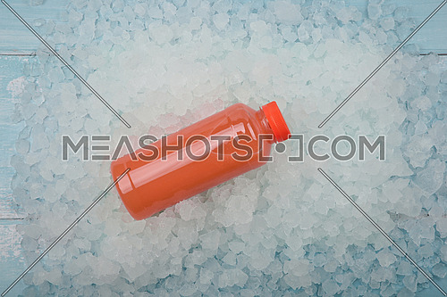 Close up one plastic PET bottle of fresh pink grapefruit juice over background of crushed ice, elevated high angle view, directly above