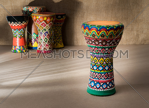 Front view of decorated colorful pottery goblet drum on background of goblet drums, wooden table with vanishing shadow lines, and sackcloth wall