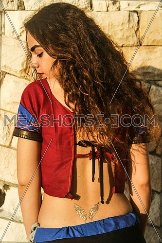 A girl stadning against a brick wall with back to the camera in an Indian outfit