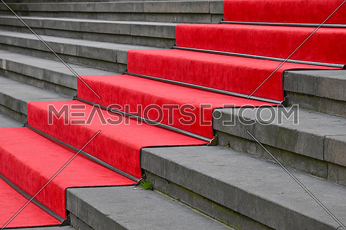 Close up red carpet over grey concrete stairs perspective ascending, low angle side view