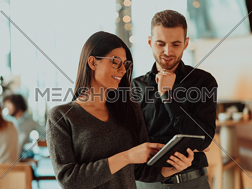 a portrait of two businesspeople standing in an office and using a tablet