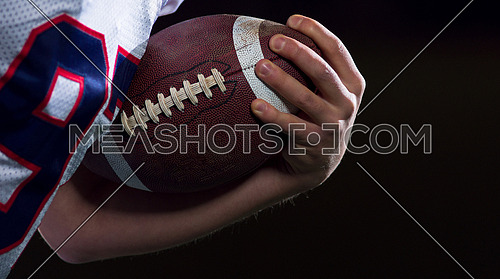 American football player holding ball while running on field at night