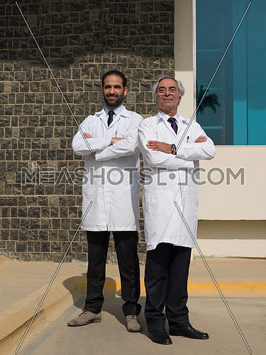 portrait of young and senior doctor in front of modern hospital