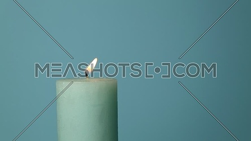 Close up one blue candle trembling flame over light blue background, off-center, fired up with lighter, burning and extinguished by woman hand