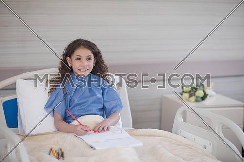 little middle eastern girl painting home and family at hospital bed in a large modern hospital