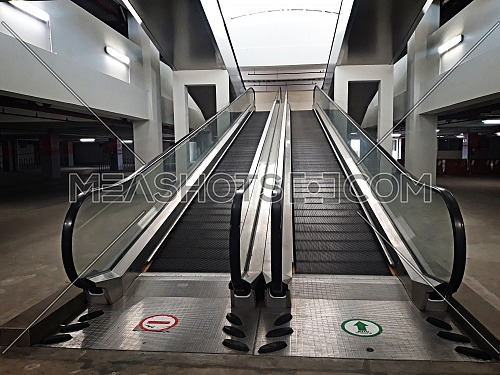 Empty double escalator inside the building with a sign on the floor