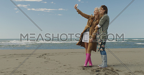 Friends making selfie. two beautiful young women making selfie at autumn day on the beach