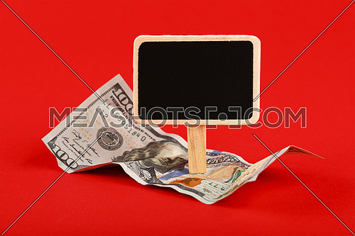 Close up one hundred US dollar paper currency banknote and blank chalk blackboard sign with copy space over red background, high angle view