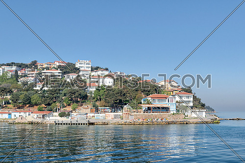 View of Burgazada island from the sea with summer houses. The island is the third largest one of four islands named Princes' Islands in the Sea of Marmara, near Istanbul, Turkey