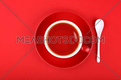 Full cup of black tea on porcelain saucer with white ceramic spoon over vivid red paper background, close up, elevated top view, directly above
