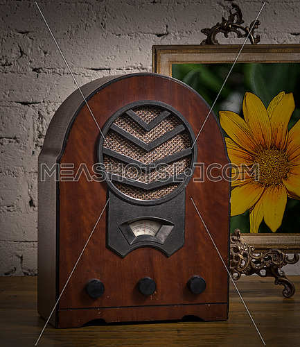 Vintage still life of an old analogue wooden radio and golden framed painting on a wooden table and background of white painted brick wall