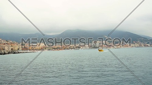 Small yellow boat sails in the bay of the port of Varazze on a cloudy day,Background Varazze town , Liguria Italy