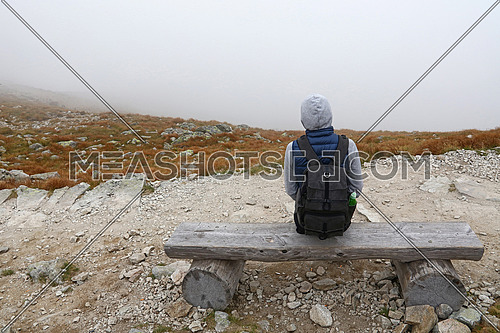 One young tourist woman with backpack sitting on wooden bench and resting on mountain road cold foggy weather day, high angle rear view