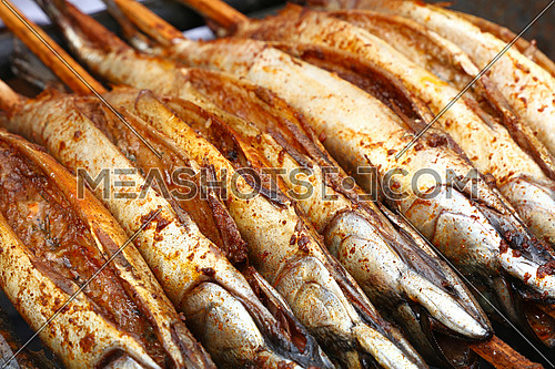 Close up cooking several bonito mackerel fishes on wooden skewer grill, high angle view