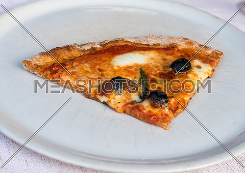 In the picture a slice of pizza with tomato, mozzarella cheese and olives served on a white dish at the restaurant.