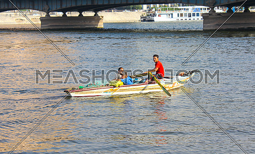 3 fisher men in a small fishing boat in the river nile