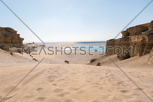 Footprints in sand desert with rock sides with under way lake view in sunlight blue sky , Fayoum , Egypt