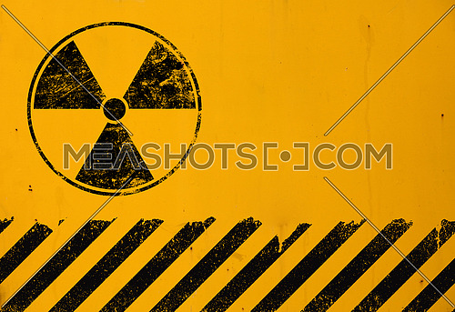 Black radioactive hazard warning sign painted over grunge yellow metal wall background with copy space