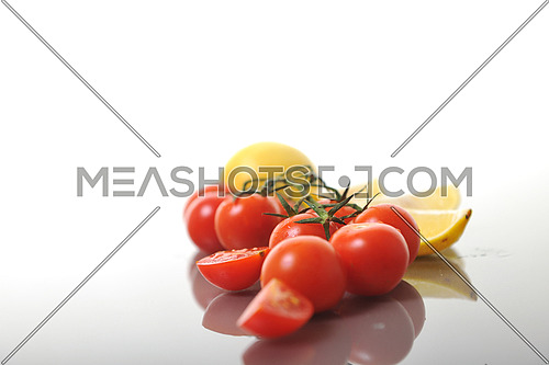 fresh lemon and tomato fruit isolated on white with reflection and fresh water drops