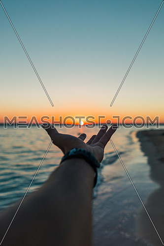Hand holding the sun by the beach, sunset