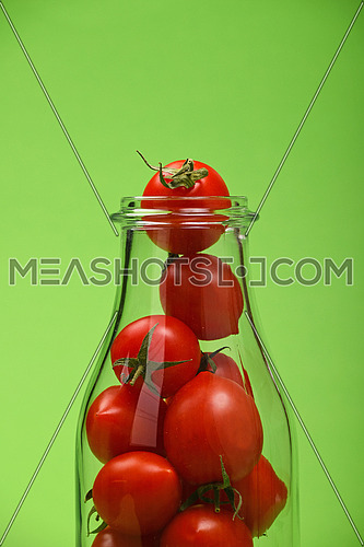 Big glass bottle full of red cherry tomatoes over green background as symbol of fresh natural organic juice or ketchup, close up crop
