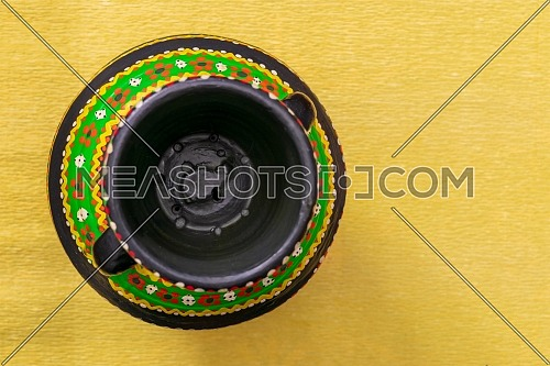 Top view of a colorful Egyptian handcrafted artistic pottery vase on yellow background
