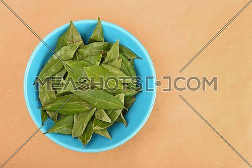 Blue ceramic bowl of green bay laurel leaves on brown kraft paper background
