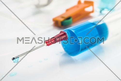 Syringe with drop of medication in the needle, conceptual image