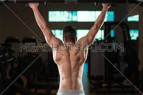 Young Male Bodybuilder Doing Heavy Weight Exercise For Back