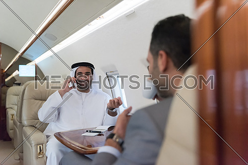 Young middle eastern successful businessman enjoyed by talking with Arab business partner while sitting in private jet