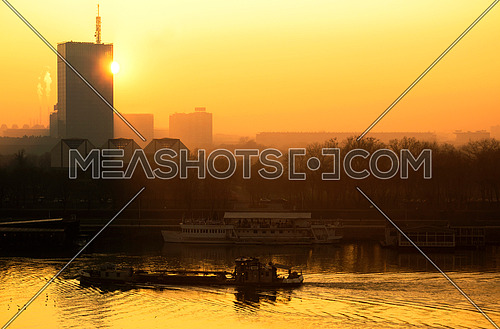 Sun going behind the building and view of the river Sava with thanker ship and urban scape of Belgrade city