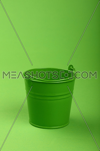 One small green painted metal empty toy bucket over green paper background, close up, high angle view