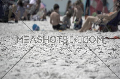 a busy beach with kids playing