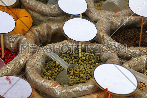 Close up several canvas bags of assorted spices, red rose pepper, green peppercorns, with copy space of blank price tags on retail display of market stall, high angle view
