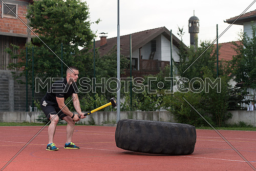 Young Man Hits Tire - Workout Outdoors With Hammer And Tractor Tire