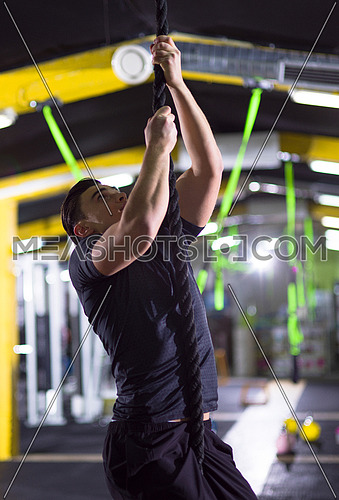 young muscular man doing rope climbing in crossfitness gym