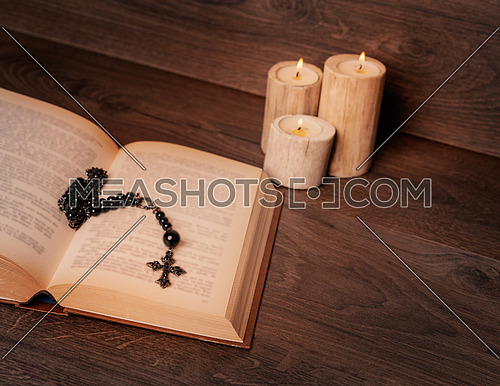 Black rosary and cross on the Bible at wooden table,background candle. Religion at school.vintage style.