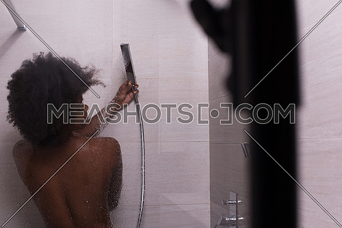 Woman in the shower,beautiful black young female showering under refreshing water, healthy lifestyle, enjoying time in luxury spa resort
